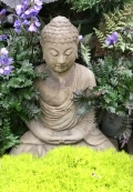 Buddha quietly sitting in a bed of green moss