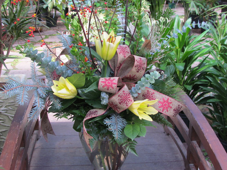 Holiday flowers with mixed evergreen and ribbon