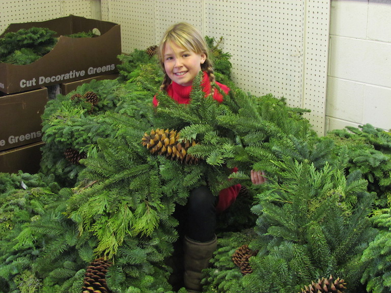 Tatum with evergreen garland and wreaths