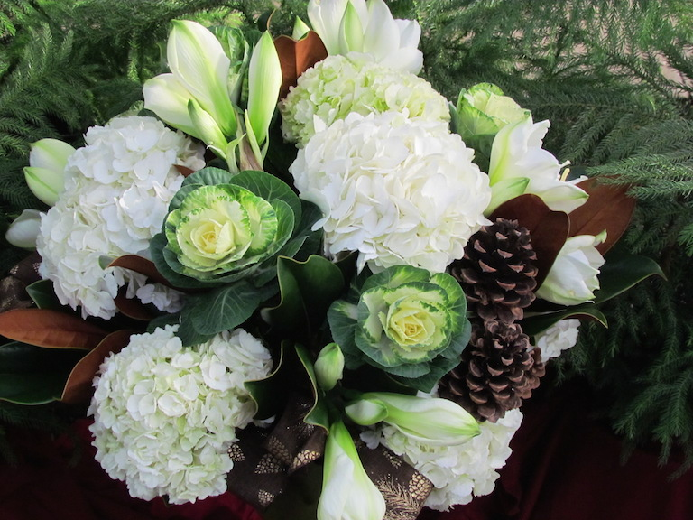 White hydrangea and flowering kale with magnolia leaves.