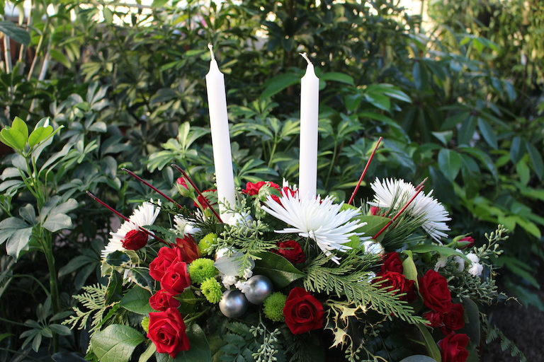 White spider mums and roses with mixed evergreen and white candles