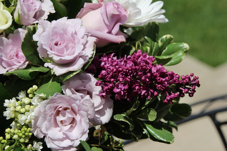 A fragrant arrangement of deep purple lilacs and lavender roses