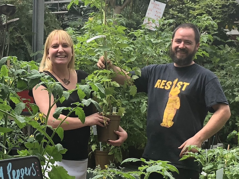 Jenn and Trevor in the greenhouse with tomato plants