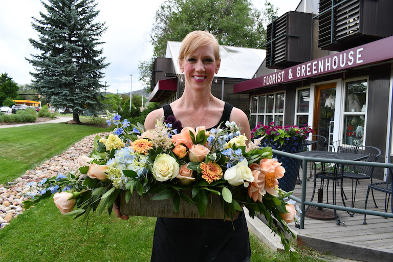 Mandy with a wedding centerpiece with peach peonies