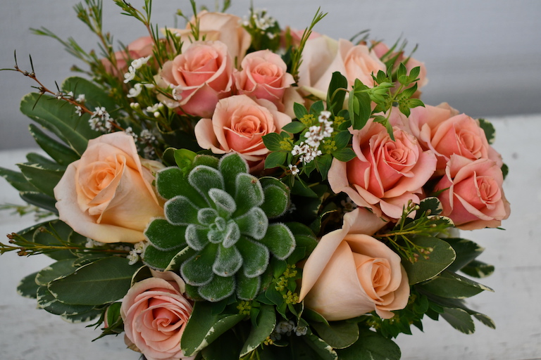 Peach roses and succulents for the bride